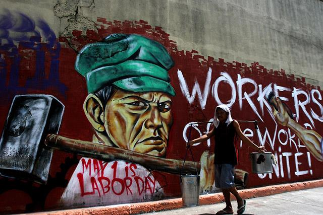 "Grafitti of man holding hammer that says ""Workers of the World Unite"""